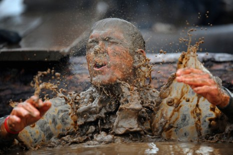 A-competitor-in-fancy-dress-emerges-from-muddy-water-during-the-Tough-Guy-Challenge-endurance-race-in-Perton-England-on-January-29-2012.-Every-year-thousands-of-people-run-the-8-mile-assault-course-which-inv