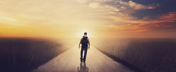 man-walking-down-road-to-sunrise